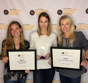 Three women stand against step and repeat backdrop holding framed certificates and award