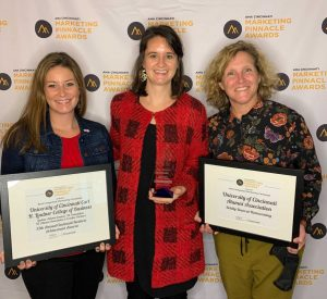Three women stand in front of step and repeat backdrop holding awards and framed certificates
