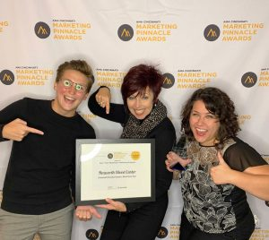 Three women stand in front of step and repeat backdrop pointing to framed certificate with excited expressions